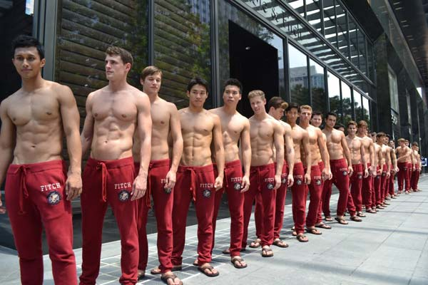 Abercrombie and Fitch staff displaying muscle in a line up outside