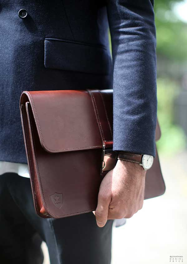 Brown man bag and a watch